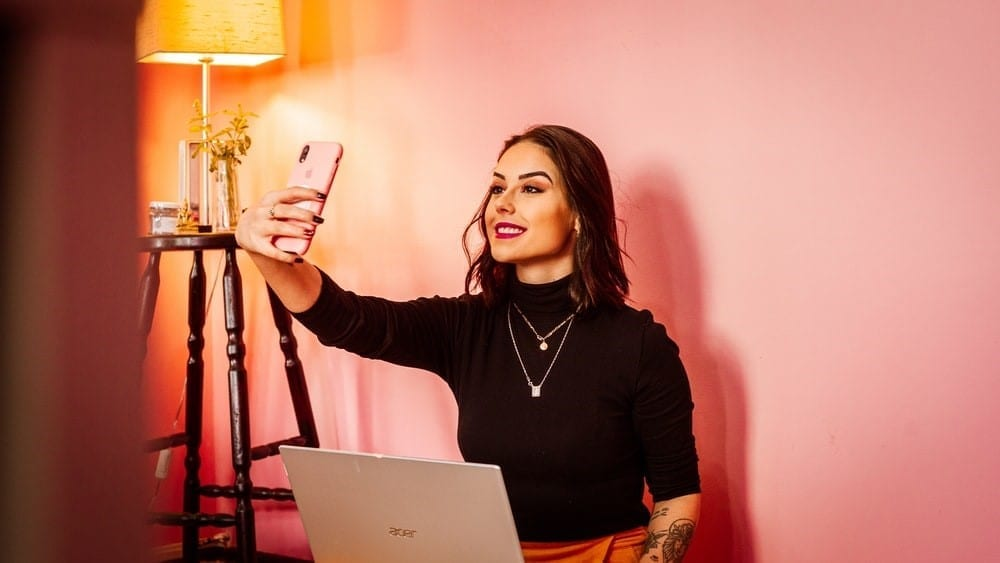 A social media influencer taking a picture of herself.