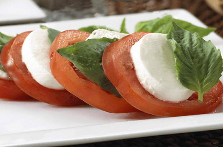 Pizzaria Caprese Salad with tomatoes, mozzarella and basil on white plate